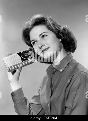 1960ER JAHRE PORTRAIT LÄCHELND TEENAGER-MÄDCHEN KIPPEN KOPF ZU TRAGBAREN RADIO HÖREN IN HAND ZUM OHR GEHALTEN - Stockfoto