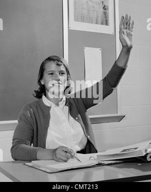 1960ER JAHREN LÄCHELND TEEN MÄDCHEN SITZEN KLASSENZIMMER SCHREIBTISCH HEBEN IHRE HAND - Stockfoto