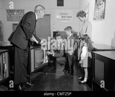1960ER JAHRE FAMILIE IM SHOWROOM VERSUCHEN FERNSEHER BEIM VERKÄUFER UHREN - Stockfoto