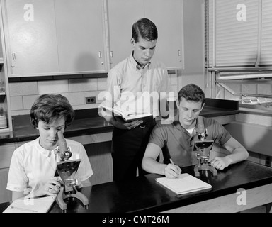 1960ER JAHREN DREI STUDENTEN, DIE MIT MIKROSKOPEN ZWEI JUNGEN EIN MÄDCHEN INNEN HIGH SCHOOL - Stockfoto