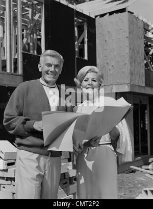 1960S 1970S LÄCHELND ÄLTERES PAAR HOLDING BLUEPRINTS HAUSBAU BAUSEITS - Stockfoto