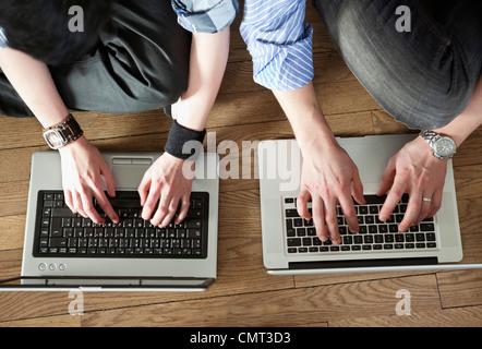 Zwei Menschen, die Eingabe auf laptop - Stockfoto