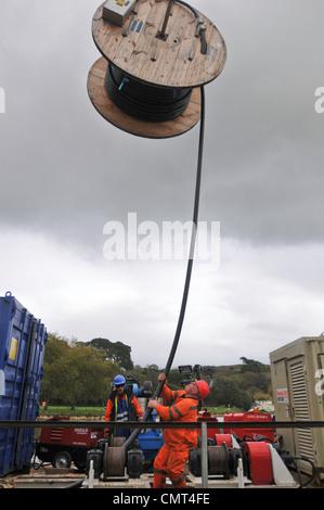 Arbeiter laden Kabel auf Lastkahn, Truro, Cornwall, England, UK - Stockfoto