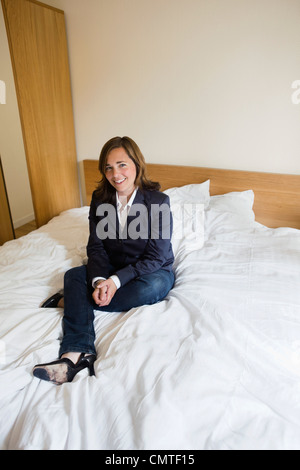 Stets gut gelaunte Frau sitzt auf Bett - Stockfoto