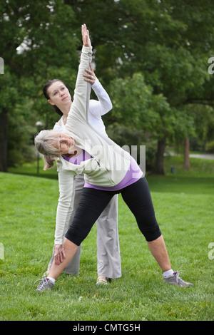 Trainer helfen Frau bei der Ausübung der im park - Stockfoto