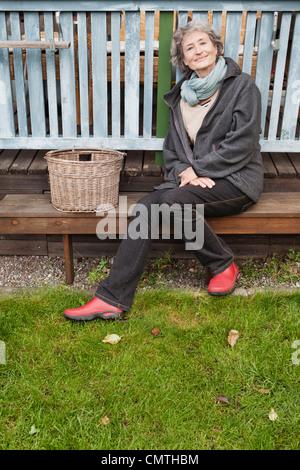 Porträt von senior Frau sitzen auf Bank Blick in die Kamera - Stockfoto