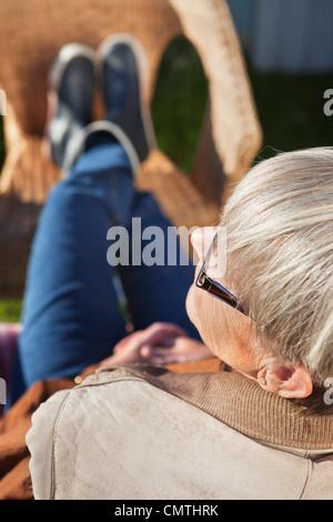 Ältere Frau ruht auf Stuhl - Stockfoto