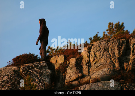 Silhouette der Mann in der Haube auf den Felsen bei Sonnenuntergang - Stockfoto