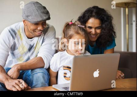 Familie mit einem Kind (6-7) Blick auf laptop - Stockfoto