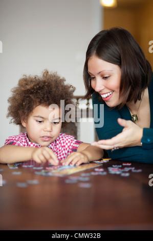 Mädchen und Mutter machen eine puzzle - Stockfoto