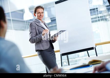 Eine Geschäftsfrau von Whiteboard stehen und blickte auf ihre Partner - Stockfoto