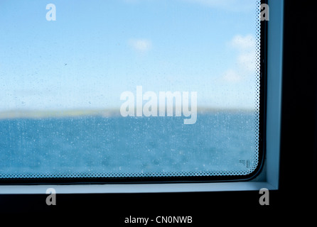 Eine verschwommene Sicht auf den Meerblick aus dem Fenster eine Personenfähre in Schottland - Stockfoto