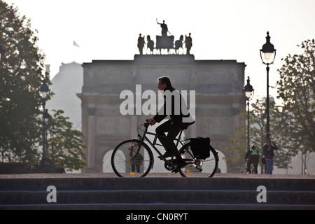 Ein am frühen Morgen Pendler Zyklen vorbei an der Arc de Triomphe du Carrousel in Jardin DesTuileries, Paris, Frankreich. - Stockfoto