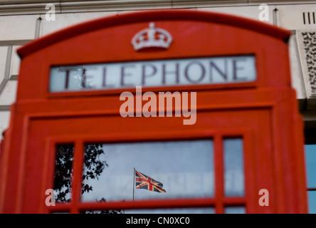 Der Union Jack (britische Flagge) spiegelt sich im Fenster eine rote Telefonzelle in London, England, am 1. November - Stockfoto