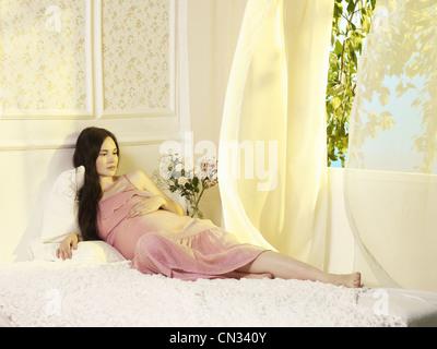 Porträt einer jungen schwangeren Frau am Fenster Stockfoto