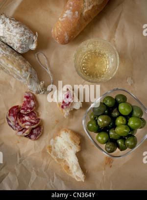Weißwein, grüne Oliven, Salami und frischem Brot - Stockfoto