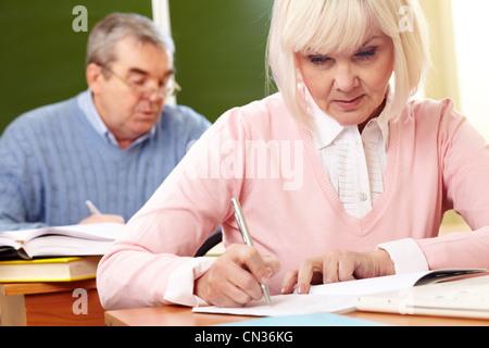 Zwei schwere Senioren tun eine Schreibaufgabe im Klassenzimmer - Stockfoto