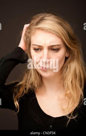 eine junge blonde 19-jährige Teenager suchen besorgt verwechselt besorgt ihr Kopf kratzen - Stockfoto
