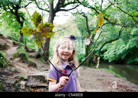 Mädchen hält einen Eiche Zweig in einem Waldgebiet - Stockfoto