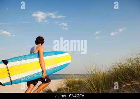 Teenager tragen Surfbretter neben Dünen Strand - Stockfoto