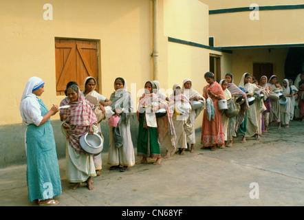 Frauen, die Töpfe im frühen Morgen Essen Schlange an Mutter Teresas Mission in Kalkutta, Indien - Stockfoto