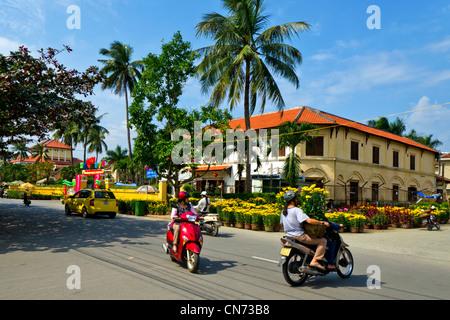 Motorrad-Verkehr fährt vorbei Gelbe Chrysanthemen zum Verkauf auf der Straße während der Tet, Hoi an, Vietnam - Stockfoto