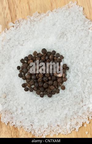 schwarze Pfefferkörner auf Steinsalz - Stockfoto
