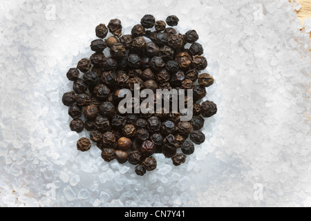 schwarze Pfefferkörner auf Steinsalz zerkleinert - Stockfoto