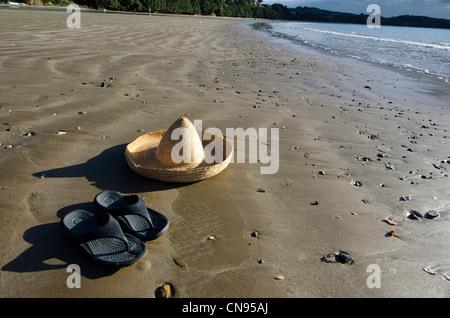 Eine leere Strand der Insel mit einem Strohhut und Paar Sandalen eines Mannes. - Stockfoto