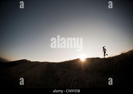 Frau läuft auf Feldweg - Stockfoto
