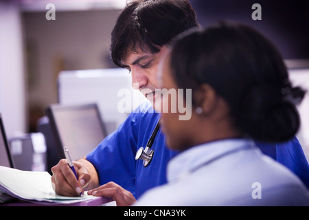 Eine asiatische Arzt arbeitet auf eine Unfall- und Emergency Unit UK - Stockfoto
