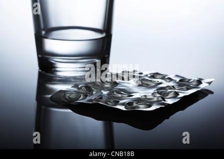 Geplatzten Blisterpackung von Pillen und Wasser - Stockfoto