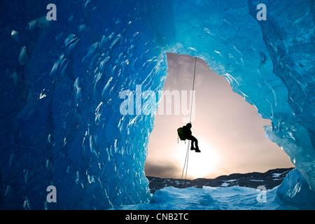 Zusammensetzung: Blick von innen eine Eishöhle eines Eisbergs als ein Eiskletterer unten Mendenhall Gletscher, Alaska - Stockfoto