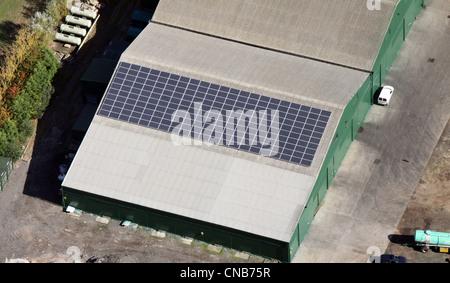 Luftaufnahme von Sonnenkollektoren auf ein landwirtschaftliches Gebäude - Stockfoto