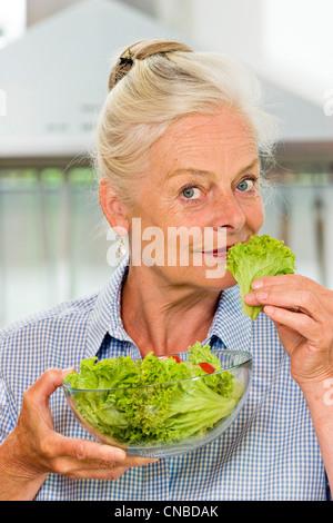 Ältere Dame, die einen Salat machen - Stockfoto
