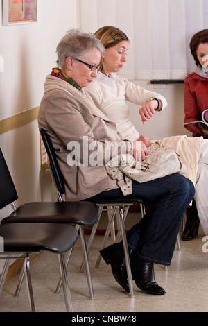 Frau auf der Suche auf ihre Uhr im Wartezimmer eines Arztes - Stockfoto