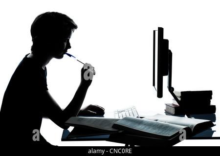 eine kaukasische junger Teenager Silhouette junge oder Mädchen studieren mit Computer Computer Laptop im Studio - Stockfoto