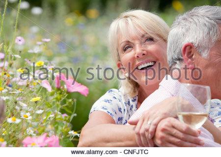 Älteres paar trinken Wein und Picknick im Frühjahr Feld - Stockfoto