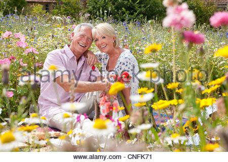 Älteres paar Picknick und Essen Erdbeeren im Bereich der Wildblumen lächelnd - Stockfoto