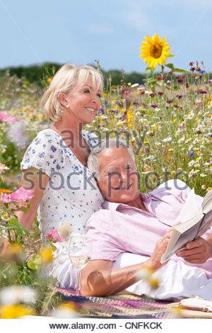 Senior woman Verlegung mit Frau und Lesebuch im Bereich der Wildblumen - Stockfoto