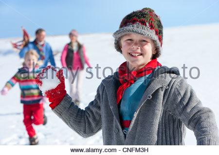 Porträt eines lächelnden jungen Schneeball mit Familie im Hintergrund halten - Stockfoto