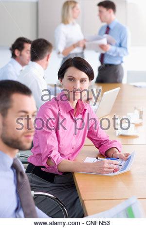 Porträt von zuversichtlich Geschäftsfrau hält Bericht unter Kollegen im Konferenzraum - Stockfoto
