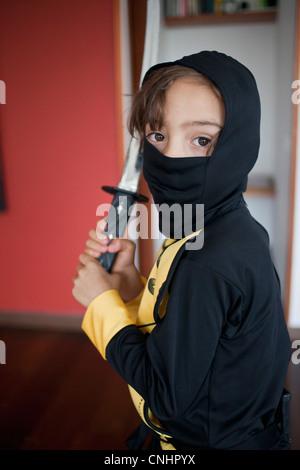 Ein Junge, gekleidet in einem Ninja-Kostüm mit einem Samuraischwert - Stockfoto