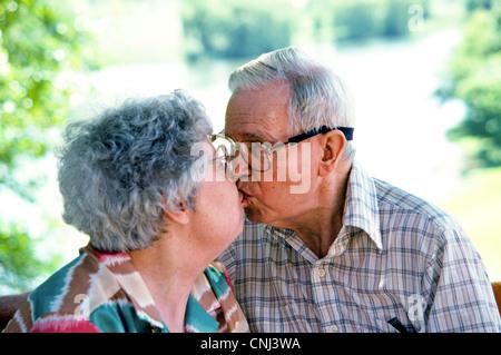 Ein älteres amerikanisches Ehepaar Kräuseln für einen Kuss feiern ihren 50. Hochzeitstag an einem sonnigen Sommertag. - Stockfoto