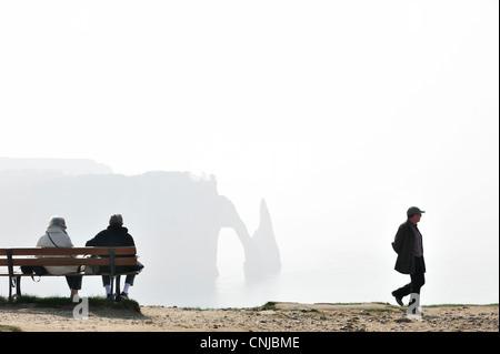 Ältere Touristen sitzen auf Bank, Blick auf die Porte D'Aval, natürlichen Bogen in Kreidefelsen bei Etretat, Haute - Stockfoto