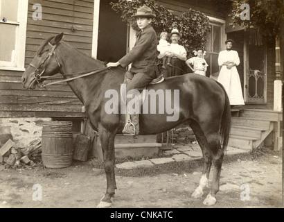 Unsichere junge auf dem Pferderücken sah von seiner Familie - Stockfoto