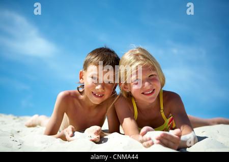 Foto von glücklich Geschwister auf Sand liegen und Blick in die Kamera - Stockfoto