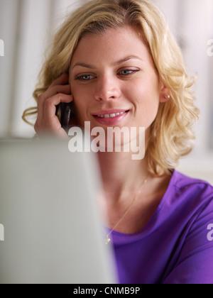Porträt des jungen schöne kaukasischen blonde Frau mit Laptop-Computer arbeiten und am Telefon zu sprechen. Textfreiraum - Stockfoto