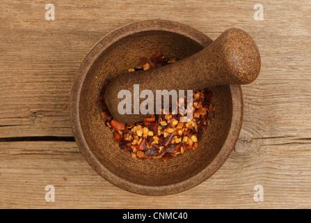 Getrocknete Chilischote in einem Stößel und Mörser auf einem alten verwitterten Holzbrett als Flocken - Stockfoto