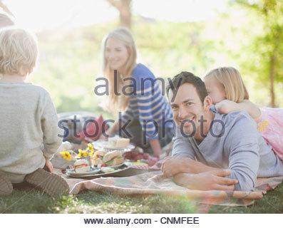 Familie gemeinsam auf dem Rasen picknicken - Stockfoto